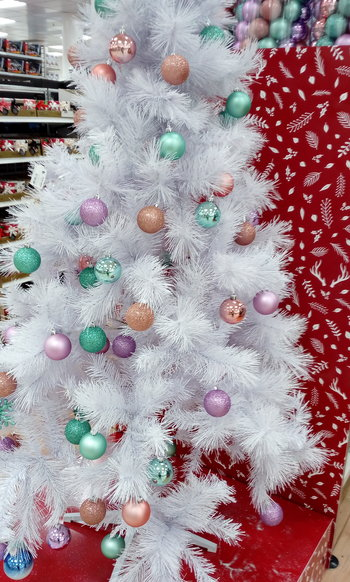 A white Christmas tree with coloured baubles